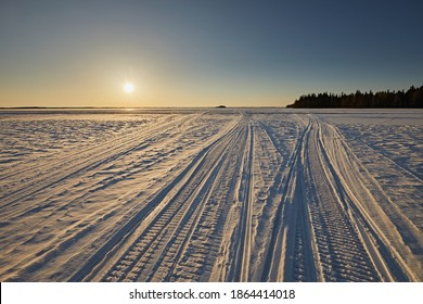 Snowmobile tracks in the snow against a sunset sky. Abstract lines on the surface