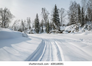 Snowmobile trail on the frozen forest river