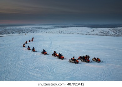 Snowmobiles in motion. Lapland, Finland.
