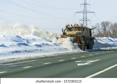 Snowplow cleans the highway from snow on a frosty day