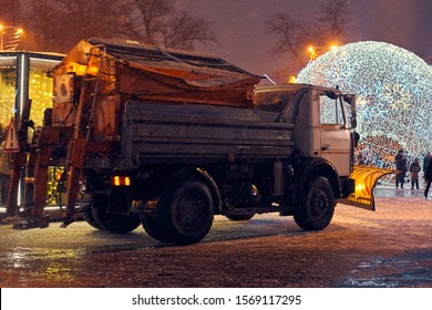 snowplow cleans the street at night. weather snowfall