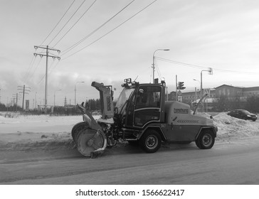 Snowplow cleansside ofthe road in  city. Black and white shot. Surgut, Russia - November 19, 2019.