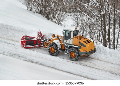 Snowplow machine clearing snow from roads after heavy snowfall in the Alps