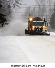 A snowplow in motion on a dark and snowy morning.