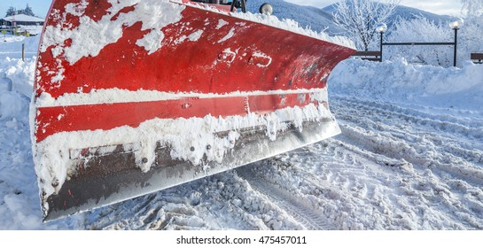Snowplow paddle cleaning the snowy road, closeup shot