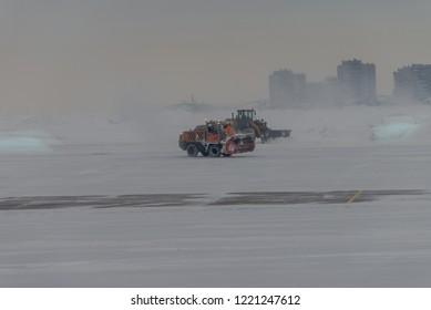 Snowplow removing snow from runways and roads in airport during snow storm, view through window
