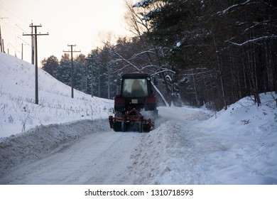 Snowplow, tractor removes snow on the road, near the forest.