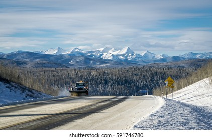 Snowplow truck cleaning mountain road after winter snowstorm blizzard for vehicle access, Alberta, Canada