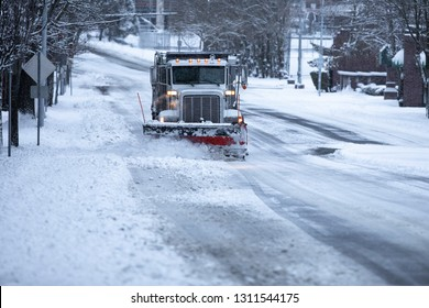 Snowplow truck plowing a snow and ice covered street, in a winter transportation background with space for text on the bottom