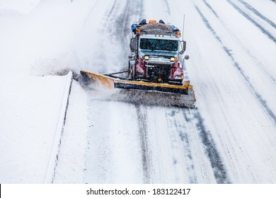 Snowplow Truck Removing the Snow from the Highway during a Cold Snowstorm Winter Day