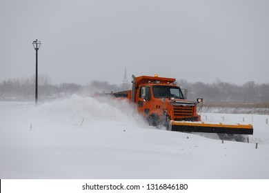 Snowplow truck removing snow on the street road in Minnesota