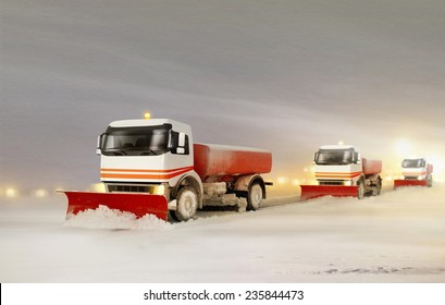 Snowplow Trucks Removing the Snow from the Highway during a Cold Snowstorm Winter Day