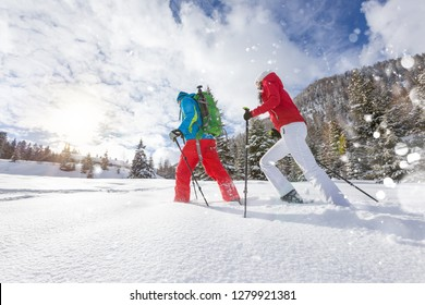 Snowshoe walkers running in powder snow with beautiful sunrise light. Outdoor winter activity and healthy lifestyle