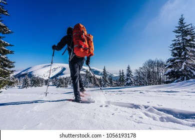 Snowshoeing in deep powder snow. Winter outdoor activity in the mountains. Hiking on snowshoes on a trail. Man trekking in snow covered mountain landscape using snowhoes and trekking poles. Slovakia.