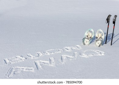 "snowshoes and sticks on the snow with ""Happy New Year"" text in Italian."