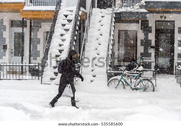 Snowstorm in Montreal. Pedestrian walking on a sidewalk.