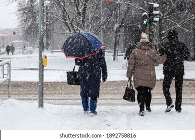 In snowstorm people cross the street. Winter, frost and urban environment