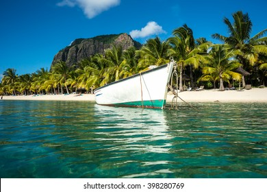 snow-white fishing boat parked in the clear emerald ocean on a background of high mountains and palm trees. Indian Ocean, Mauritius island