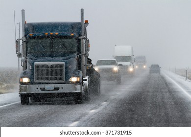 snowy afternoon on a busy highway with traffic and low visibility for a winter caution concept