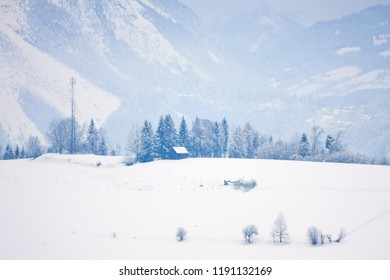 Snowy alpine landscape with bare trees and cottages
