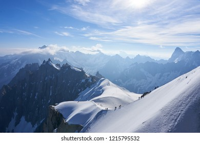 Snowy Alpine landscape (Europe) with mountaineers at the top of the mountains