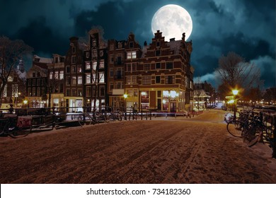 Snowy Amsterdam by night in the Netherlands by full moon