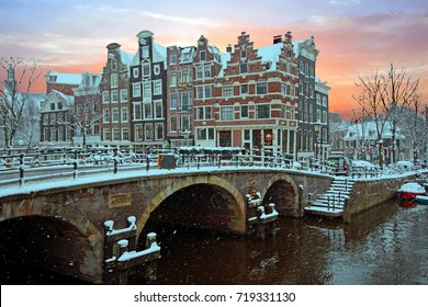 Snowy Amsterdam in the Netherlands in winter at sunset