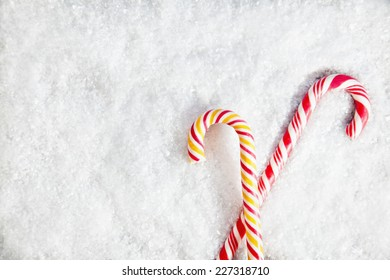 Snowy Background With Two Candy Canes . Copy Space