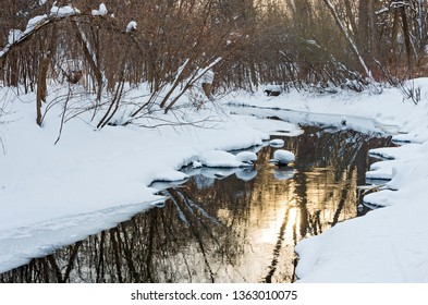 snowy banks of minnehaha creek flowing through woodlands of minnehaha parkway and sun reflecting off water in minneapolis minnesota