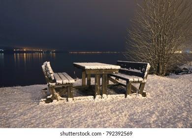 Snowy bench near water. Fjord of Drammen.