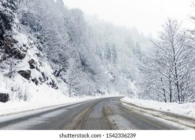 Snowy bending road scene in winter, with snowy trees, rocks and asphalt road.