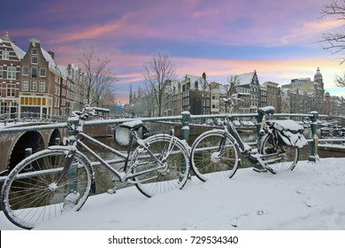Snowy bicycles in Amsterdam city center the Netherlands at sunset