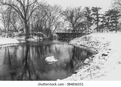 Snowy black and white scene with river and train bridge