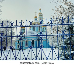 Snowy blue Orthodox Church behind the blue fence in winter
