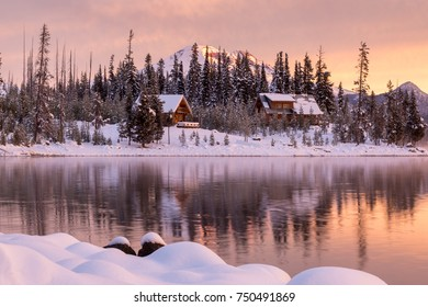 Snowy cabins line the shore of Elk Lake in Bend, Oregon during a colorful sunrise.