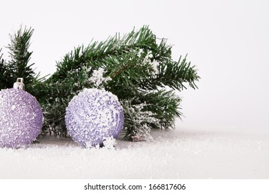 Snowy christmas decoration objects with ornaments and balls on white background.