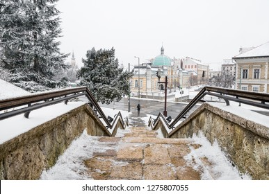 Snowy cityscape with stone stairs leading down from a hill to a lonely person in the city center of Miskolc
