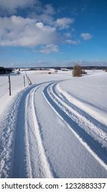 snowy country road in rural landscape, blue sky with clouds. road trip in winter landscape bavaria