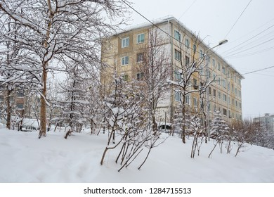 Snowy courtyard with a panel building. After the snowfall there are big snowdrifts around trees and bushes. Snow on the branches. Cold winter weather. Magadan, Siberia, the Far East of Russia.