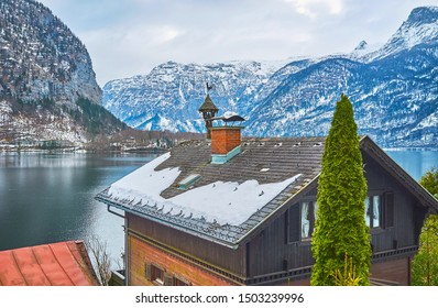 The snowy Dachstein Alps and dark waters of Hallstattersee lake behind the old house roof with a chimney and vintage weather vane with bell and figurine of rooster, Hallstatt, Salzkammergut, Austria