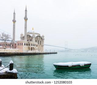 Snowy day in Ortakoy, Istanbul, Turkey. View of Ortakoy Mosque and Bosphorus Bridge.