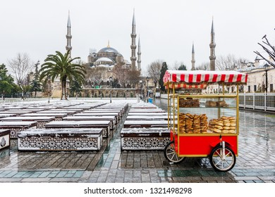 Snowy day in Sultanahmet Square. Blue Mosque (Sultanahmet Camii) and Turkish Bagel Seller. Istanbul, Turkey.