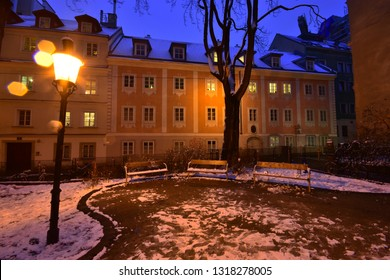 Snowy evening mood at deserted park lit by a street lamp at Spittelberg in Vienna between historic houses of the old town in Advent. Some raindrops create an atmospheric effect.