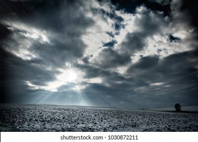 Snowy field with cloudy sky and sunrays, Czech Republic