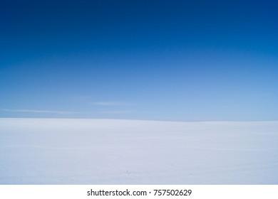 Snowy field under blue sky
