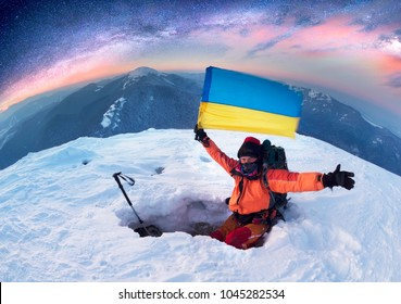 Snowy frosty top with beautiful scenery at sunset mountain range in extreme frosty weather with a lonely climber in modern mountaineering outfit in a snow cave with the flag of Ukraine