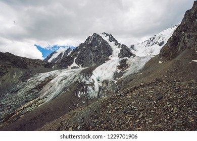 Snowy giant mountain range under cloudy sky. Rocky ridge with snow. Huge glacier. Icy mountainside with water streams. Wonderful mountains. Atmospheric minimalist mountainous landscape of nature.