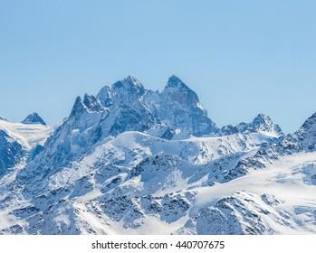 Snowy Greater Caucasus mountains Ushba and Schelda summits against sun shining in winter. Elbrus region, Kabardino-Balkaria, Russia.