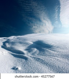 Snowy hill with deep blue sky and clouds