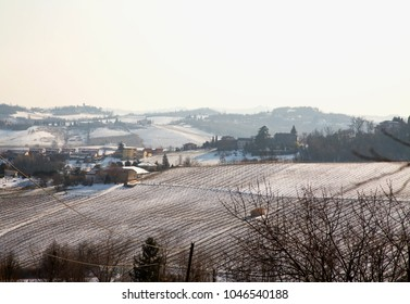 Snowy hills landscape, with fields and houses, horizontal image